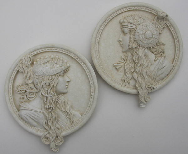A pair of round wall plaques with fine detailing in a typical art nouveau style. These wall hanging plaques are designed for both interior and exterior display. They have a metal hook on the back for hanging and are weather resistant. Made from an Iberian marble and cement mix, these plaques make an ideal choice for those that love wall art.Diameter 19 cm-