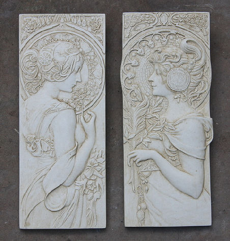 A pair of art nouveau wall plaques designed in an Alphonse Mucha style, ideal for both interior and exterior display. These lovely plaques have a hook on the back for hanging and are weather resistant. They are made from an Iberian marble and cement fondue with fine detailing to produce an outstanding feature for your home.Height 24 cm-Width 9 cm-